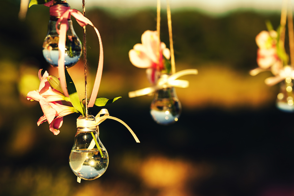 wedding decor hack, flowers in lightbulb vase used as pendant lights