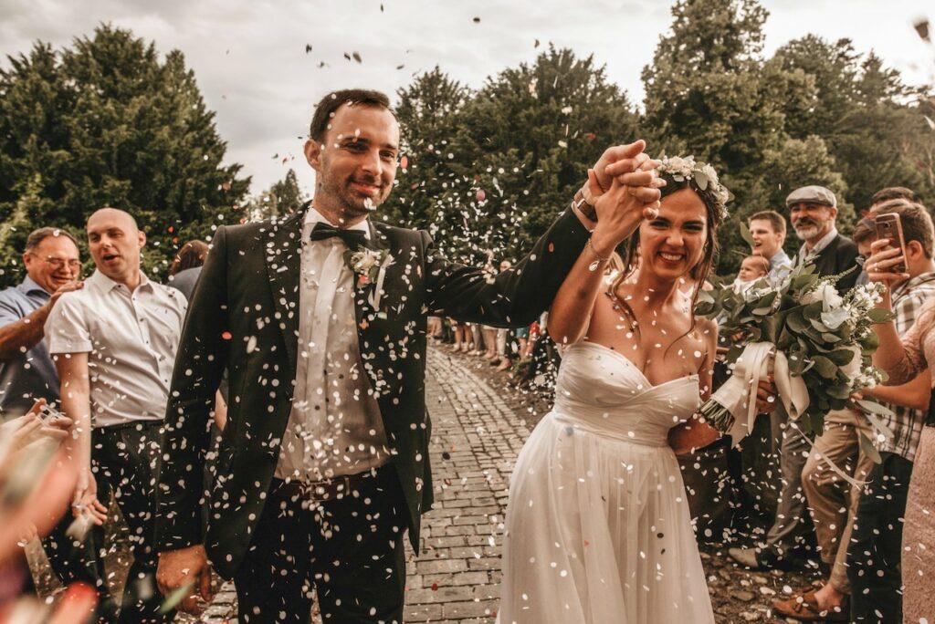 Bride and groom walking through a confetti shower.