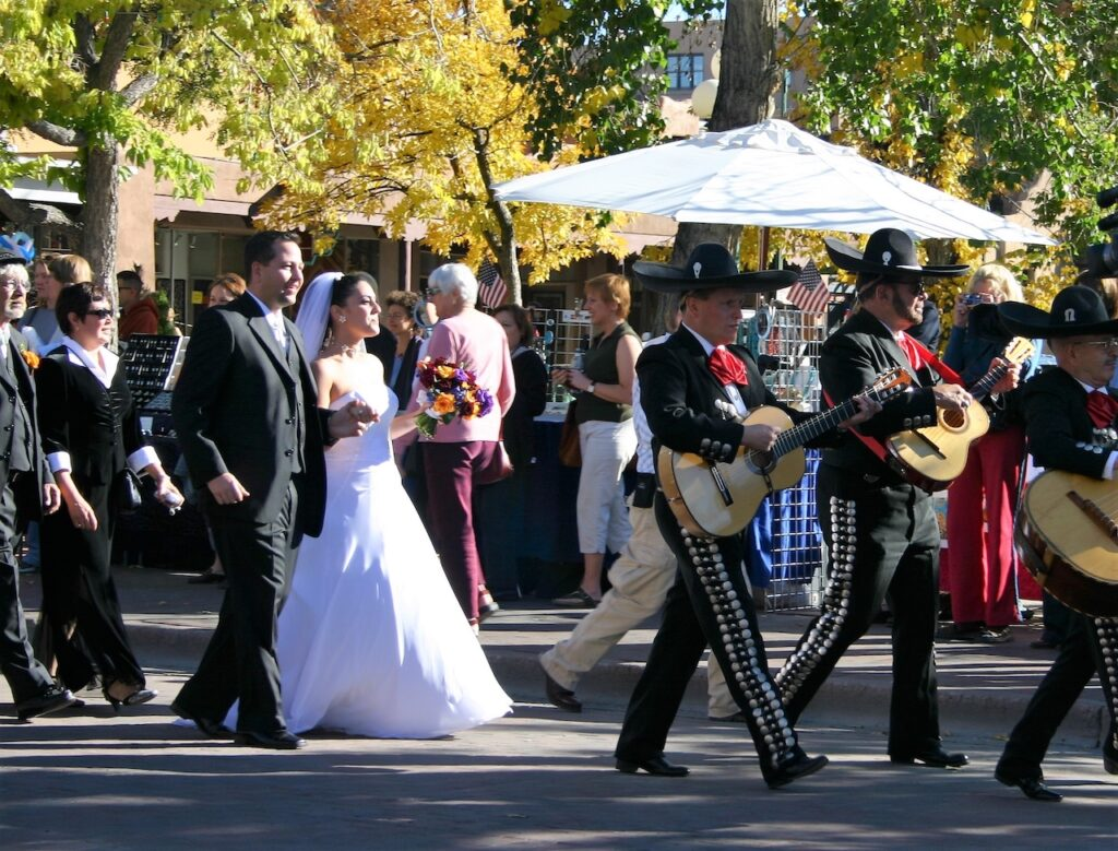 Bride and groom walking in a parade.