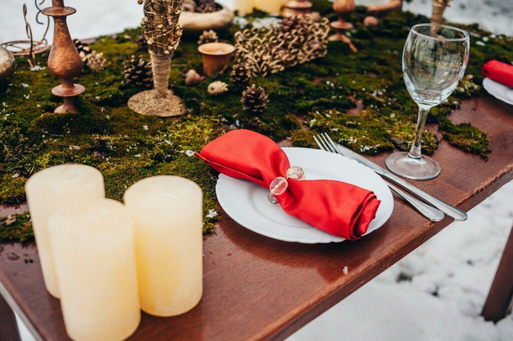 Table and dinnerware set out in the snow.
