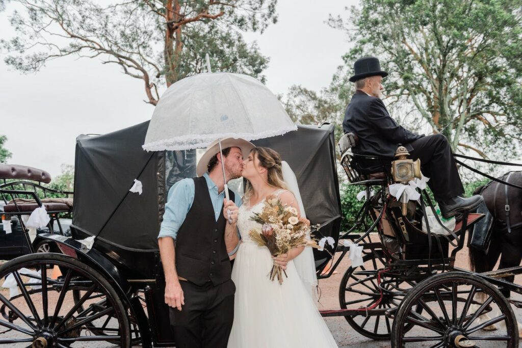 Bride and groom in front of carriage.