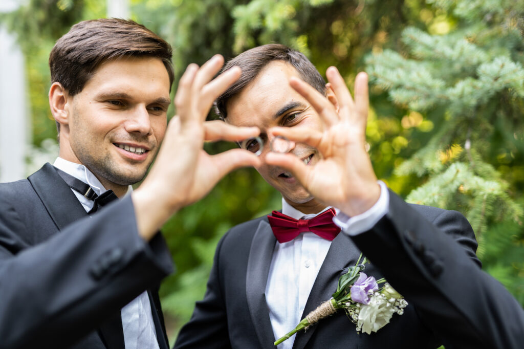 gay couple holding up wedding rings
