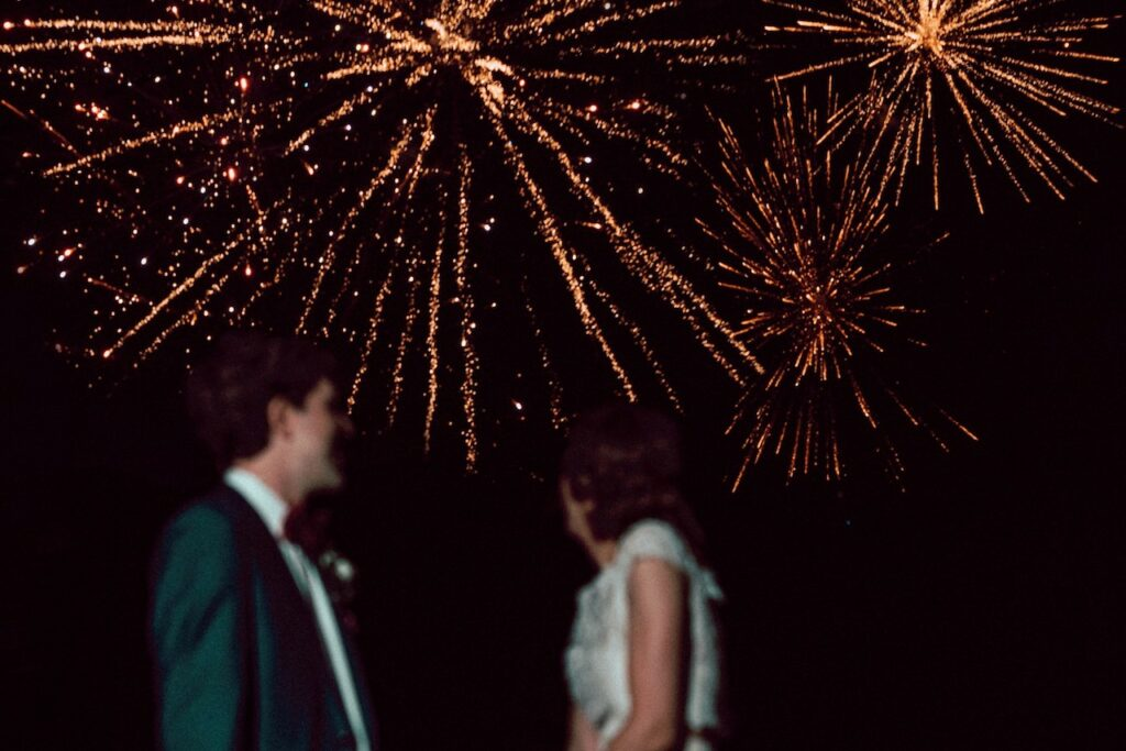 Bride and Groom standing under firework explosion.