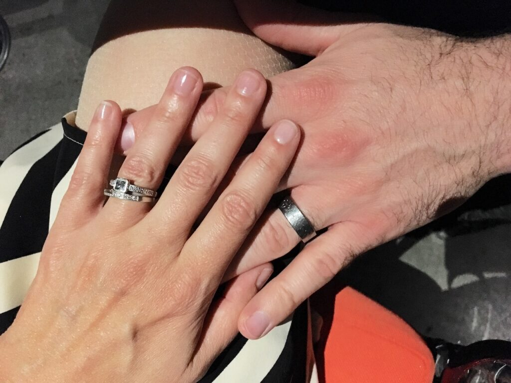 couples hands wearing wedding bands