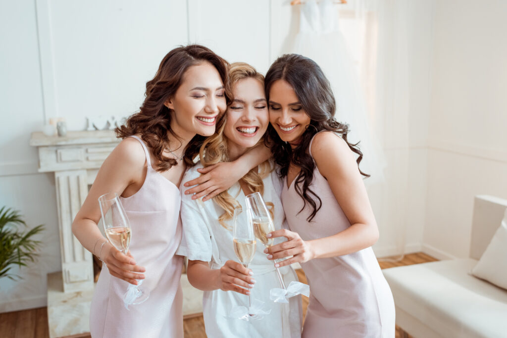two bridesmaids hugging the bride holding champagne glasses